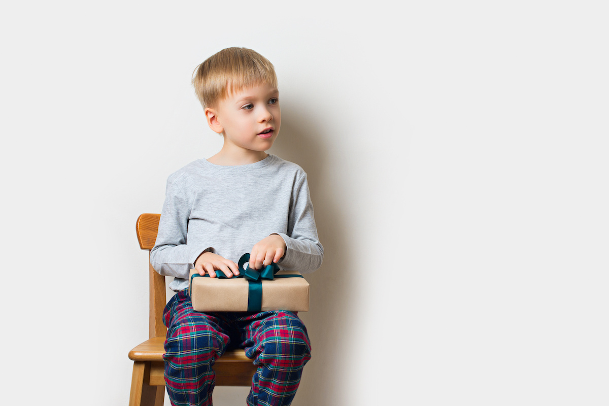 Scandinavian lifestyle minimalism christmas and new year concept with kid - little boy with stack of gift box on a chair in room, white background