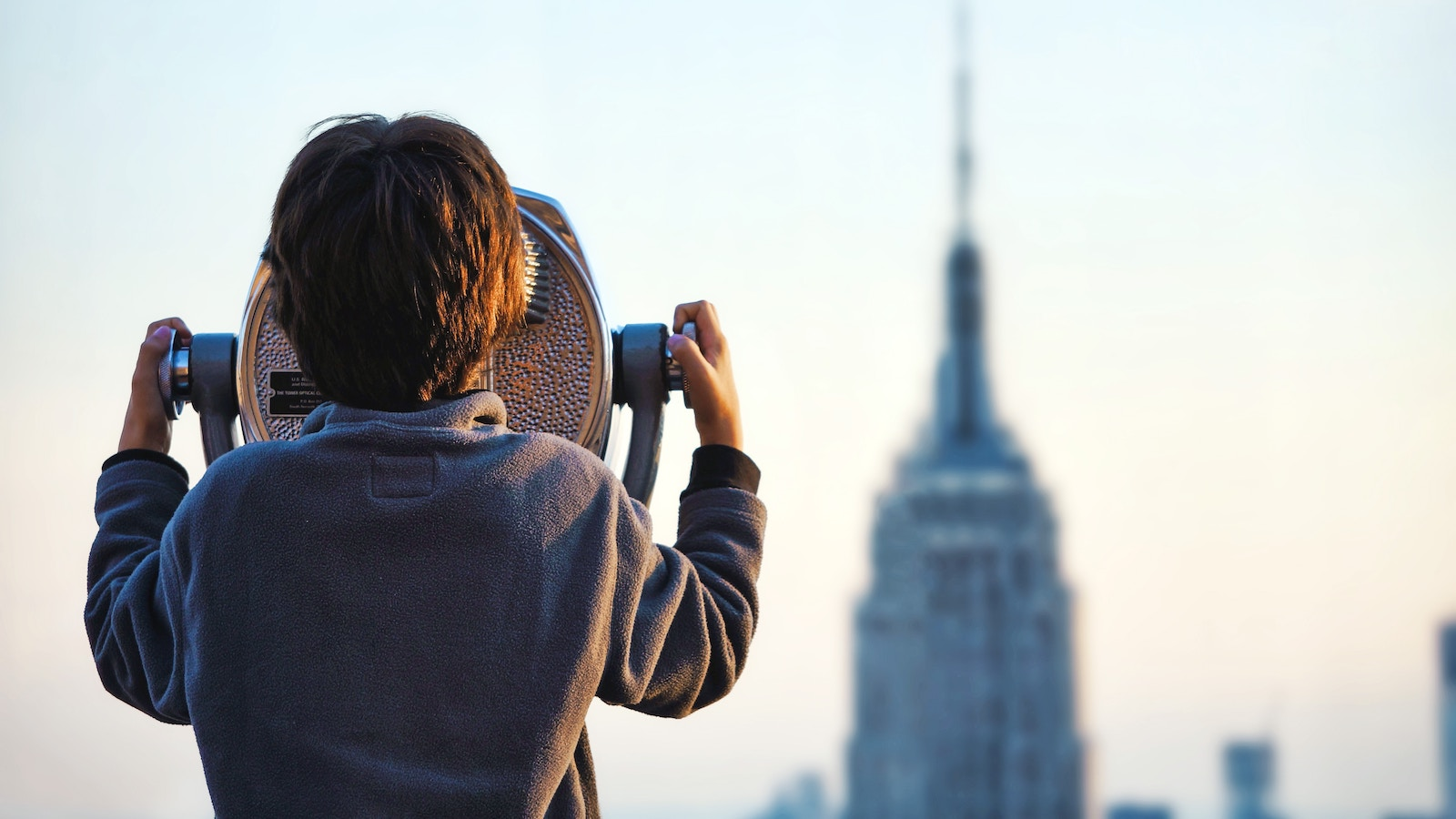 Child looks through binoculars at Empire State Building