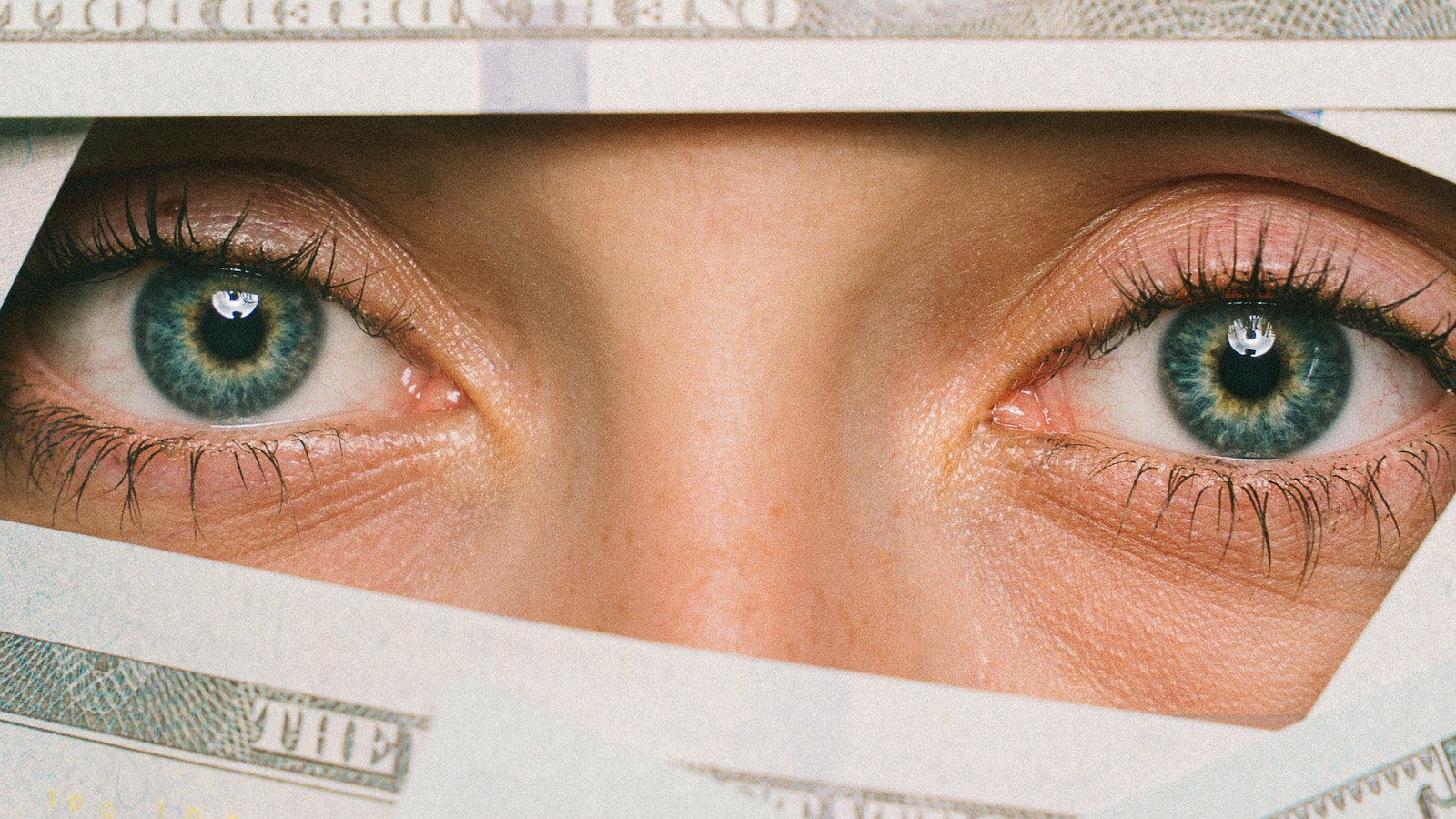 Woman eyes peeking through hundred dollar bills